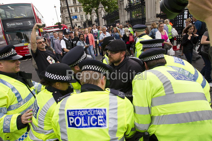Police arresting a disabled man blocking the road after a Balls To The Budget protest. Balls To The Budget, Disabled People Against Cuts throwing balls at Downing Street as George Osborne leaves to deliver his budget to Parliament. Parliament Square, Westminster. London - Jess Hurd - 2015-07-08