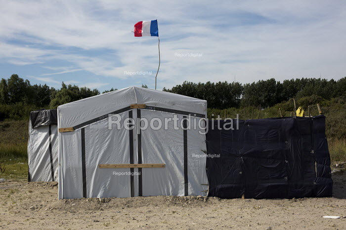 French flag flying ironically above makeshift tent Calais migrant camp The Jungle France - Jess Hurd - 2015-08-02