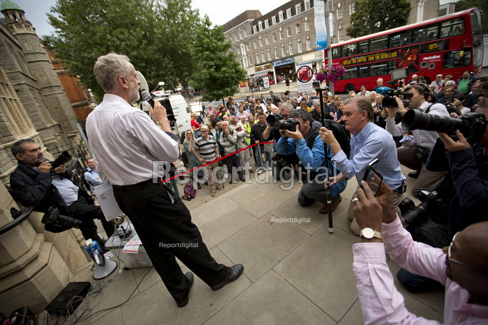Jeremy Corbyn speaking to overflow of supporters outside Ealing Town Hall before a Quiz Corbyn meeting inside. Bus advertisement reads Defeat The Empire, Join The Rebellion. London. - Jess Hurd - 2015-08-17