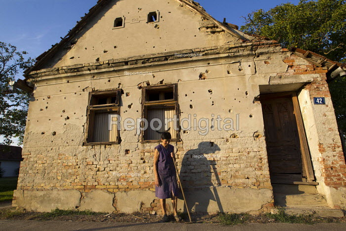 Woman poses for a photograph outside her house riddled with bullets from the war. Tovarnik. Croatia. - Jess Hurd - 2015-09-23