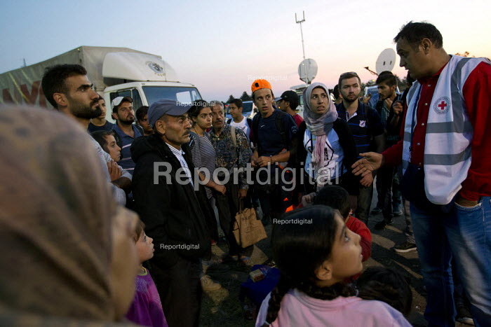 Frightened refugees who escaped the overcrowded Opatovac refugee camp talk to a Red Cross worker about the violence from the police and fighting inside the camp. Croatia. - Jess Hurd - 2015-09-22