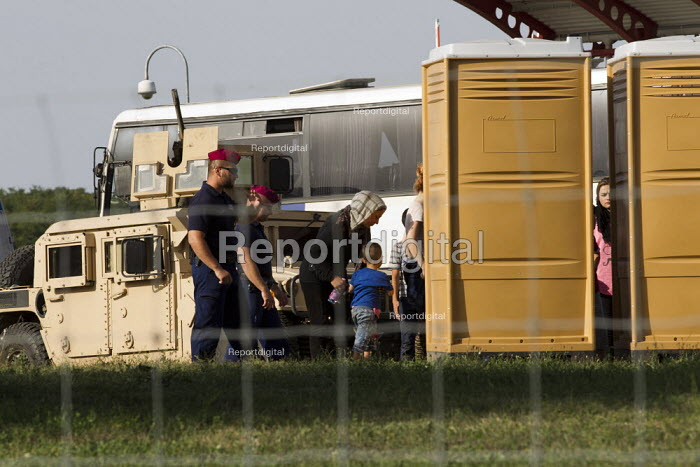 Police and military watch as refugee women and children use toilet facilities at the Beremend, Hungarian border crossing. Hungary. - Jess Hurd - 2015-09-19