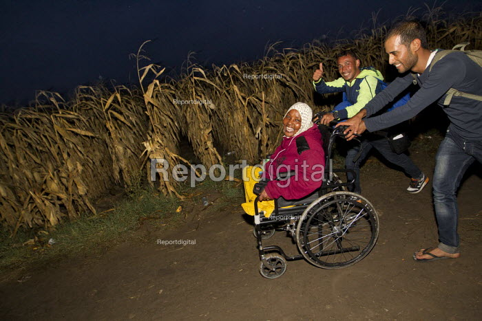 Woman with amputated legs has her wheelchair pushed through the corn fields as refugees make their way to Europe via Tovarnik, Croatia border crossing. Serbia. - Jess Hurd - 2015-09-20
