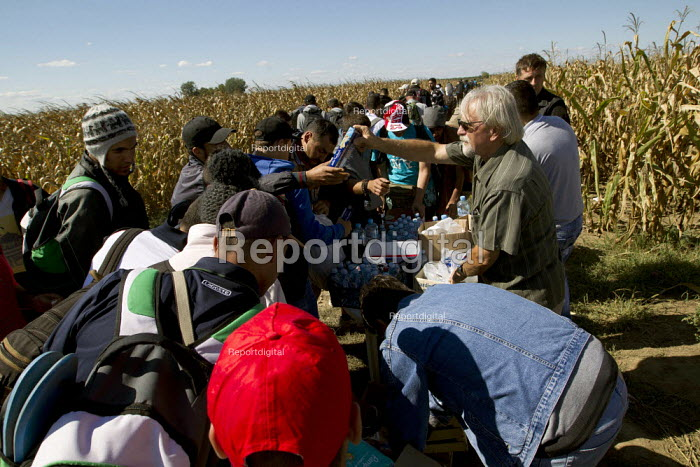 UNHCR, other NGOs and local people help supply refugees for the journey through corn fields towards the Tovarnik Croatia border crossing. Serbia. - Jess Hurd - 2015-09-21