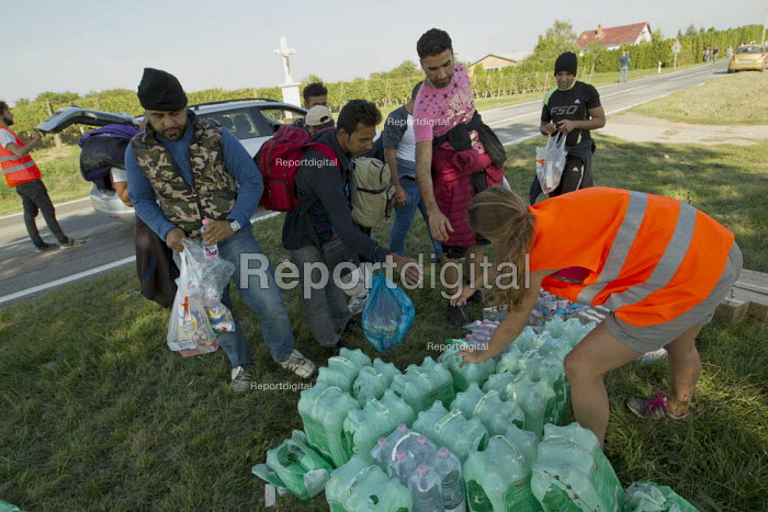 Volunteers from Germany give exhausted refugees food and water for the journey to Opatovac refugee camp. Croatia. - Jess Hurd - 2015-09-22