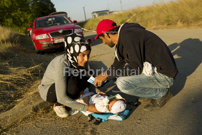 Family changing their baby on the side of the road outside Opatovac refugee camp. Croatia. - Jess Hurd - 2015-09-22