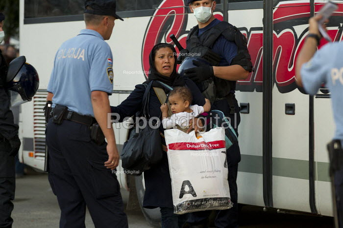 Refugees rush to board a bus to Austria after being pepper sprayed by riot police at Opatovac refugee camp. Croatia. - Jess Hurd - 2015-09-22