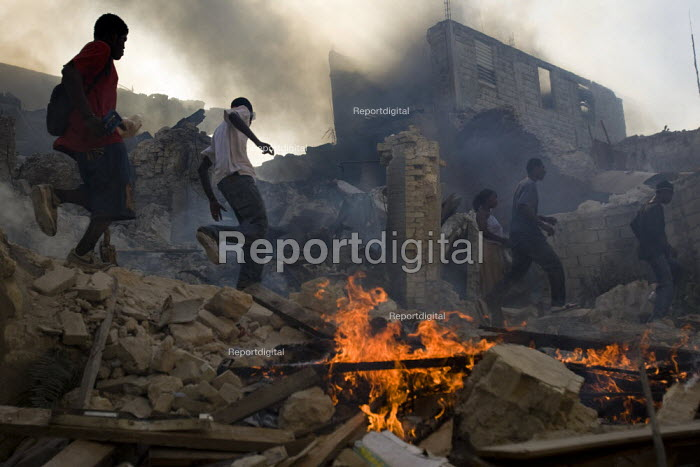 Haitians salvage food and goods necessary for survival from burning buildings. Haiti earthquake. - Jess Hurd - 2010-01-18