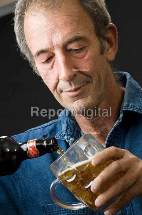 Man pouring himself a glass of beer. - Paul Carter - 2007-09-04