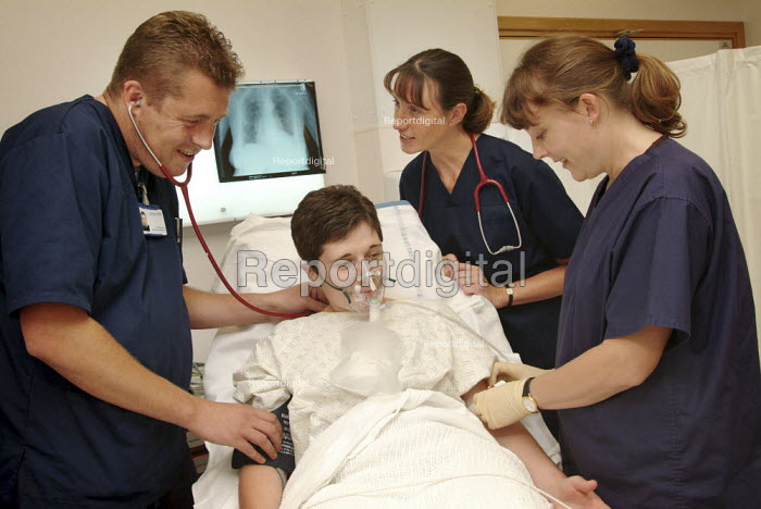 Nurse registrars training as nurse consultants, practise procedures with the help of a colleague volunteer. Accident and emergency unit. - Paul Carter - 2004-08-11
