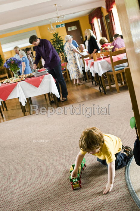Young boy playing with a train, during a family gathering at a hotel. - Paul Carter - 2008-07-19
