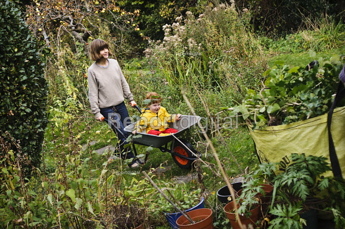 Mother and young son playing, whilst gardening. Child is having a ride in the wheelbarrow. - Paul Carter - 2008-10-04