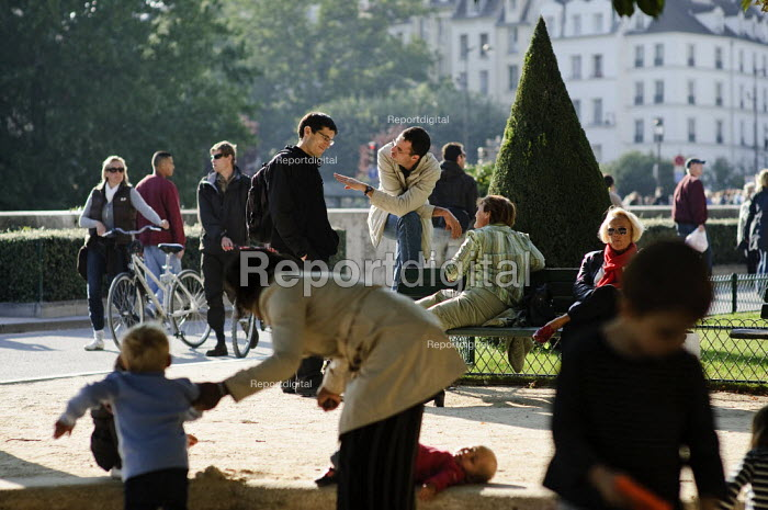 Busy French park, with people talking, walking their bikes, children with their mothers, people sitting on park benches relaxing by the River Seine.  Park and children's play area next to Notre Dame cathedral, Paris. - Paul Carter - 2008-09-19