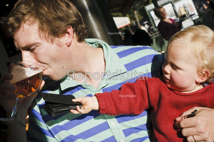 Father drinking a glass of beer in a cafe as his child passes him his wallet - Paul Carter - 2008-09-20