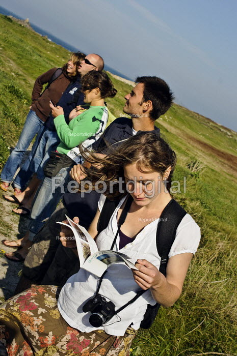 A group of people stop to admire the view and identify the wild flowers from a guide book. St, Agnes, Isles of Scilly. - Paul Carter - 2008-10-13
