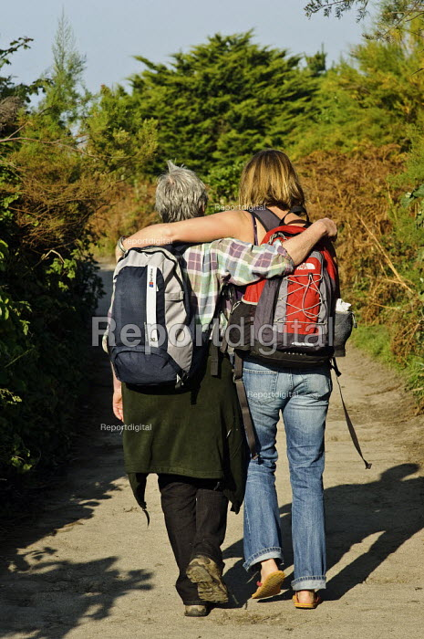 Rear view of an older and younger woman, walking with arms around each others shoulders. - Paul Carter - 2008-10-12
