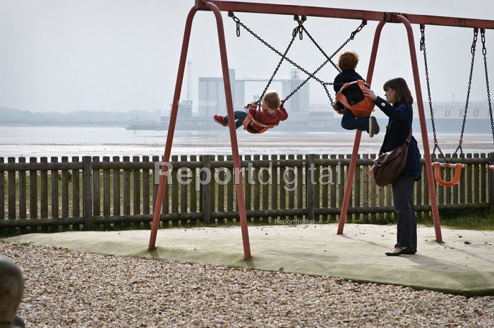 Mother pushing her two children on the swings overlooking the port of Southampton. Weston Shore, Southampton, UK - Paul Carter - 2010-06-16