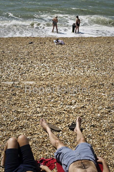 People paddling and sunbathing on a shingle beach. - Paul Carter - 2009-07-25