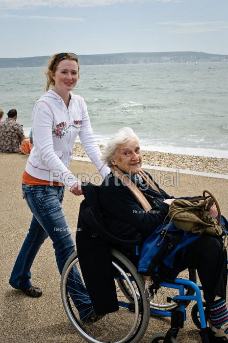 Elderly woman with her carer at Milford-on-Sea enjoy the sunshine and views across the sea. - Paul Carter - 2009-07-25