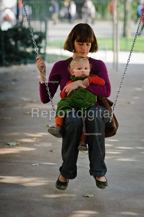 Mother and young son sitting on a swing in a city park. Paris - Paul Carter - 2008-09-19
