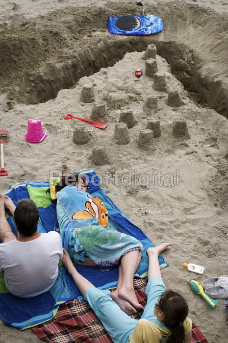 A woman asleep on a towel next to a sand castle, Looe, Cornwall, UK - Paul Carter - 2010-08-04