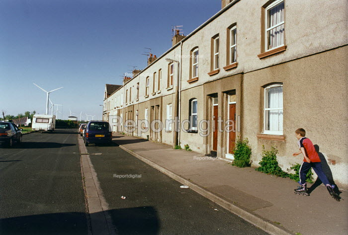 A young boy roller skating along the street by a row of terraced houses, Cumbria. Windmills from a windfarm are in the distance. - Paul Carter - 2000-07-17