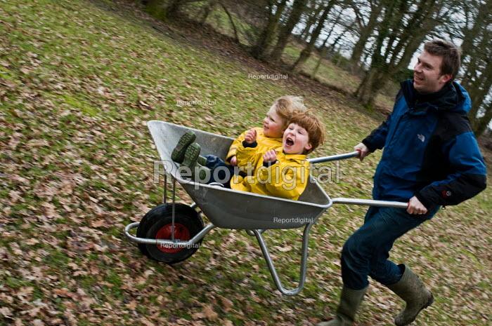 Two brothers having a ride in a wheelbarrow. They are being pushed by their father. - Paul Carter - 2010-02-26