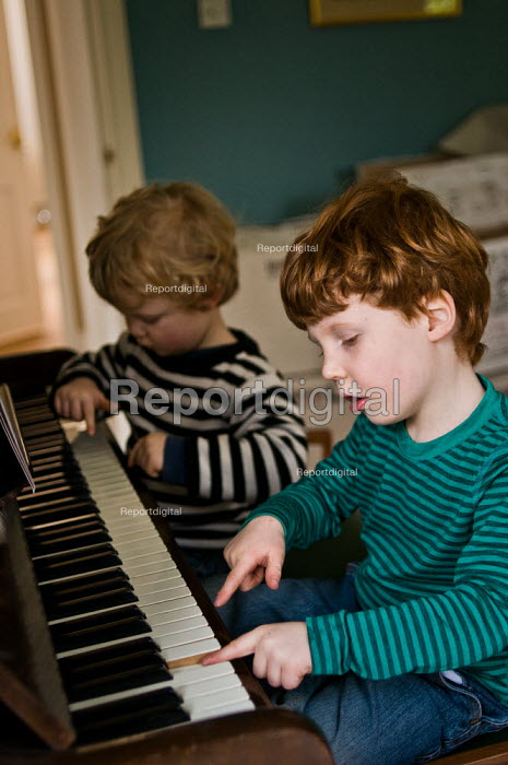 Two young boys playing the piano together in the front room at home. - Paul Carter - 2010-09-27