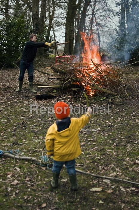 A young boy watches his father tending a garden bonfire. - Paul Carter - 2010-09-27