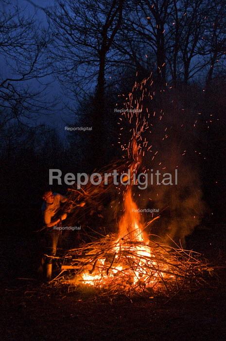 A man putting logs on a garden bonfire. - Paul Carter - 2010-09-27