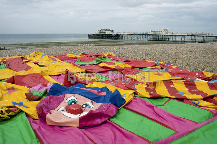 Deflated bouncy castle with Worthing Pier in the distance as the holiday season ends. Worthing, West Sussex UK. - Paul Carter - 2010-09-29