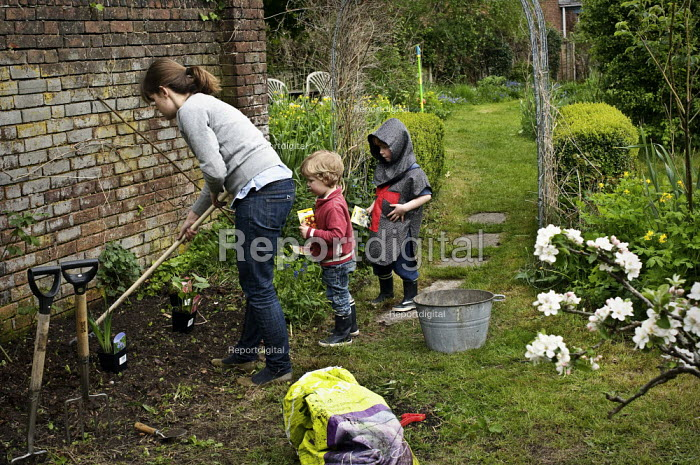 A woman plants seeds in the garden with the help of her two sons. - Paul Carter - 2010-05-01