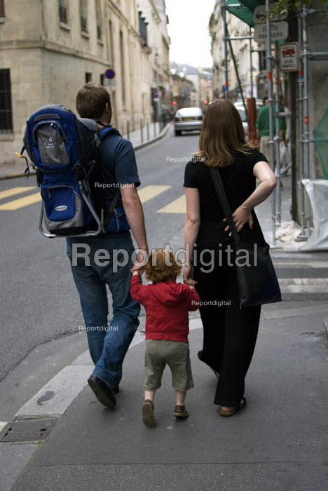 A pregnant woman, her husband and her son walking along the pavement. The woman is holding her back. On holiday in Paris, France. - Paul Carter - 2007-08-17