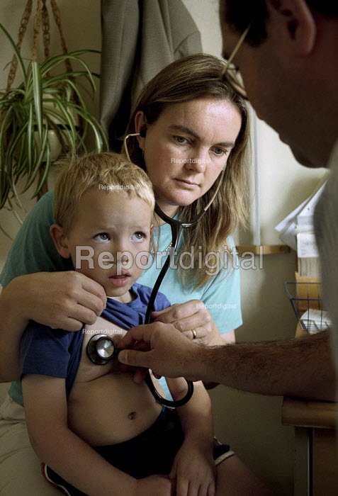 A doctor helps a mother listen to her son's chest and breathing using a stethoscope during a consultation at a GP's surgery. - Paul Carter - 2003-09-30