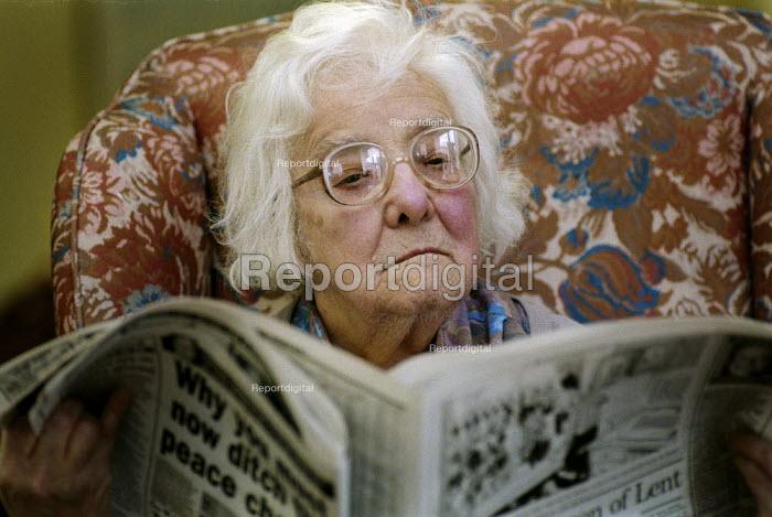 Elderly woman sitting in an armchair, reading a newspaper. - Paul Carter - 1996-02-20