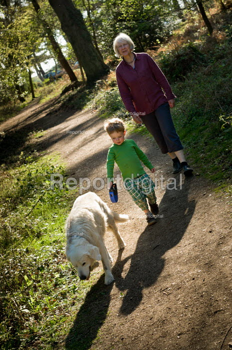A young boy and his grandmother walk a pet dog through woodland in Norley Wood, The New Forest. - Paul Carter - 2011-04-20
