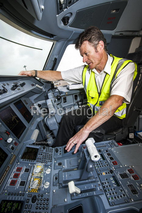 Pre-flight check. A line engineer checks the faults list on the computer in the cockpit of a FlyBe Embraer 195 passenger jet. Southampton International Airport. - Paul Carter - 2012-09-14