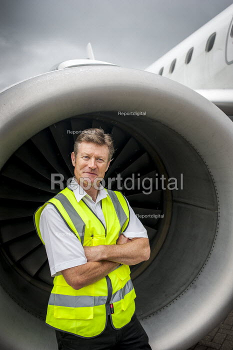 A line engineer in front of the engine of a FlyBe Embraer 195 passenger jet. Southampton International Airport. - Paul Carter - 2012-09-14