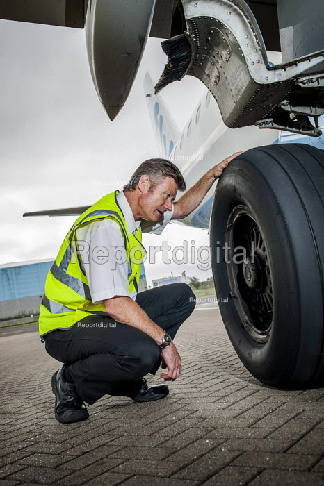 Engineer checking wheels tyres landing gear of FlyBe Embraer 195 passenger jet. Southampton International Airport. - Paul Carter - 2012-09-14