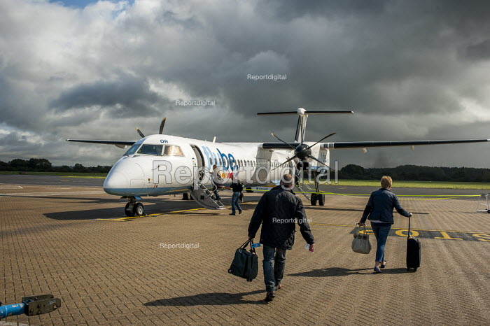 Passengers with suitcases walking across the apron to board a Bombardier Dash 8 Q400 turbo prop FlyBe passenger aircraft. Southampton International Airport. - Paul Carter - 2012-09-14