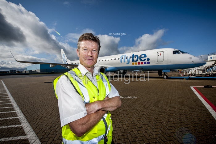 Portrait of a line engineer in front of a FlyBe Embraer 195 passenger jet. Southampton International Airport. - Paul Carter - 2012-09-14