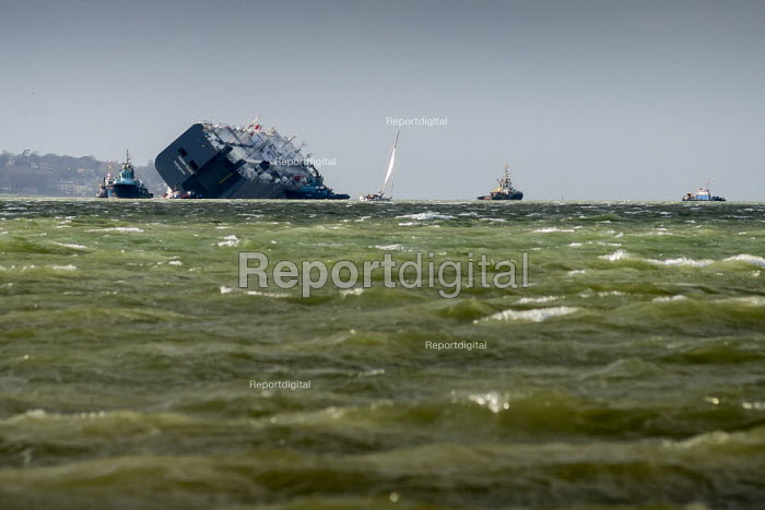 Tugs hold the vehicle carrier ship Hoegh Osaka from shifting its position in the Solent during a salvage operation. The ship had been deliberately run aground because it had started to list. - Paul Carter - 2015-01-13