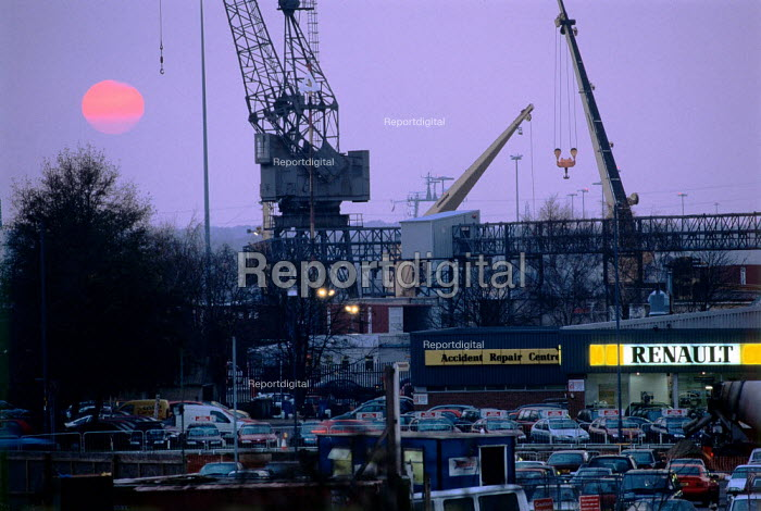 Looking over a car showroom, to cranes on the docks. Sunset, Southampton - Paul Carter - 1998-12-12
