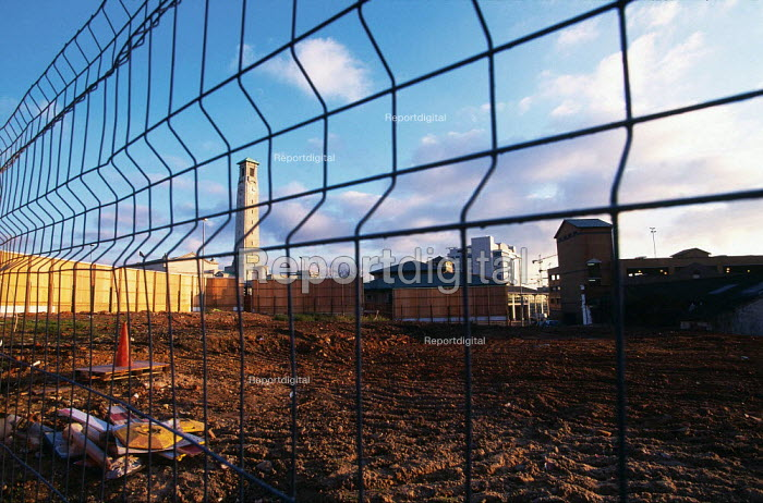 Looking through a metal mesh fence across an area of cleared land ready for redevelopment. - Paul Carter - 1998-12-12
