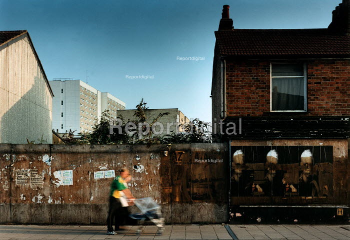 Couple with a pushchair, walk past a wall and boarded up shop window covered with posters. - Paul Carter - 1995-08-25