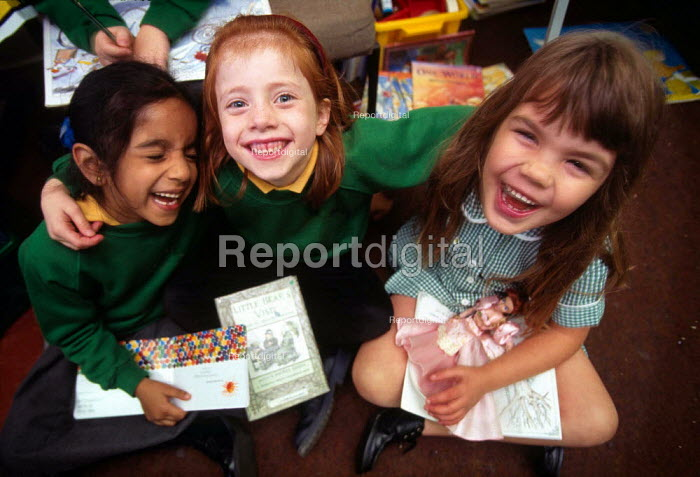 Three young school girls sitting on the floor with books on thier laps, laughing. - Paul Carter - 1999-10-20