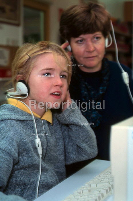 Teacher and pupil using the computer for spelling practice. They are both wearing headphones. - Paul Carter - 1999-10-20