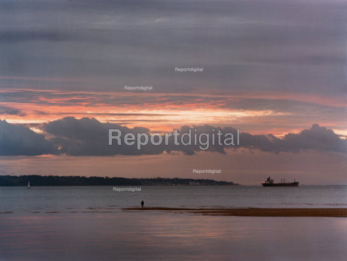 Sunset over still water with a cargo ship silhouetted on the horizon. - Paul Carter - 1999-01-28