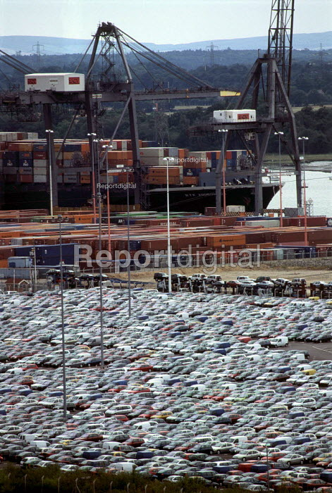 Container vessel docked alongside cranes and waiting cargo. Southampton Docks - Paul Carter - 1999-09-06