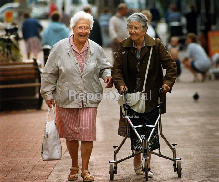 Two elderly women walking through a city centre, laughing. One is using a walking frame. - Paul Carter - 1995-09-08